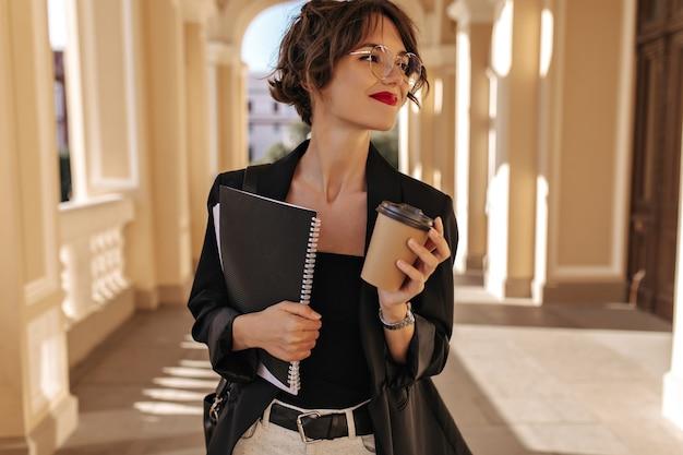 Linda mulher de óculos, segurando uma xícara de chá e um caderno do lado de fora. mulher morena com lábios vermelhos na jaqueta preta, sorrindo ao ar livre.