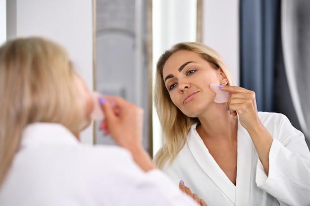 Linda mulher de roupão realizando massagem facial de drenagem linfática com massageador de pedras gua sha, massageando o rosto na direção das linhas dos músculos, olhando sua imagem no espelho