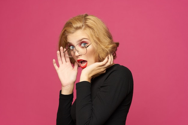 Linda mulher de suéter preto penteado curto óculos rosa fundo isolado.