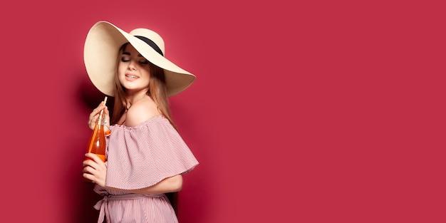 Linda mulher de vestido e chapéu de palha com bebida gelada