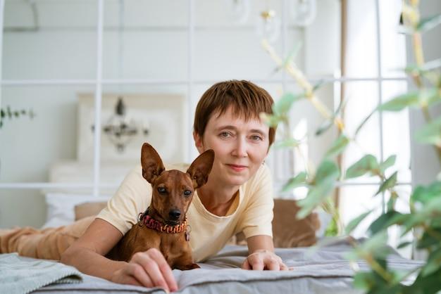 Linda mulher deitada de bruços relaxando na cama com suas amadas carícias matinais de cachorro em uma confeitaria quente.