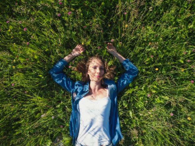 Linda mulher deitada em um campo de flores verdes