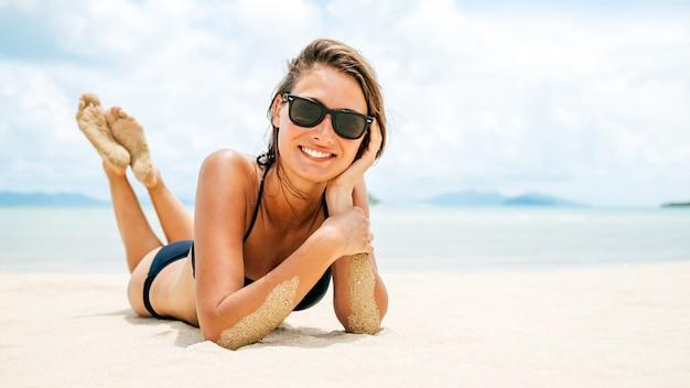 Linda mulher deitada na areia da praia