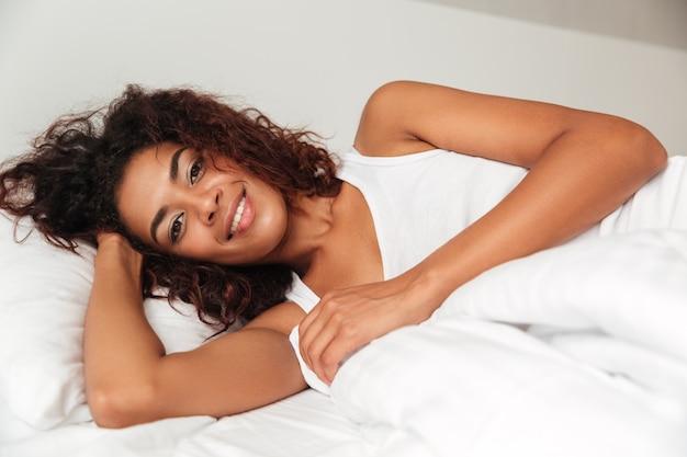Linda mulher deitada na cama com travesseiro e olhando