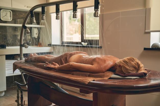 Linda mulher deitada na cama de madeira enquanto faz hidroterapia no resort