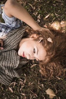 Linda mulher deitada na grama de outono