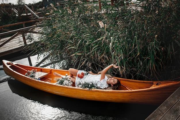 Linda mulher deitada sozinha em um barco de madeira flutuando no lago se aposentando com a natureza