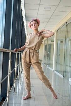 Linda mulher descalça em pé dentro do prédio olhando para a frente