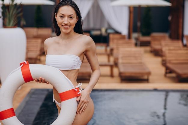 Linda mulher descansando à beira da piscina segurando uma boia salva-vidas