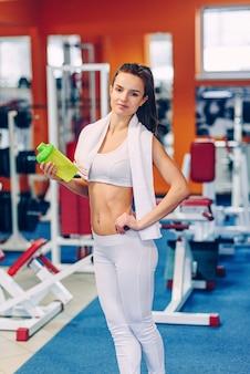 Linda mulher desportiva com corpo perfeito mantém o agitador na mão no ginásio