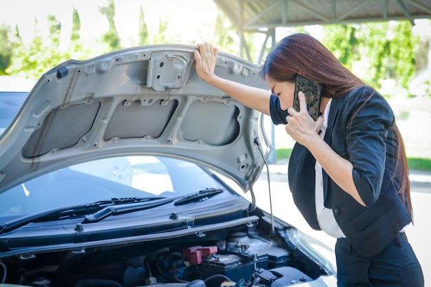 Linda mulher dirigindo para o trabalho mas seu carro está quebrado chamando um reparador
