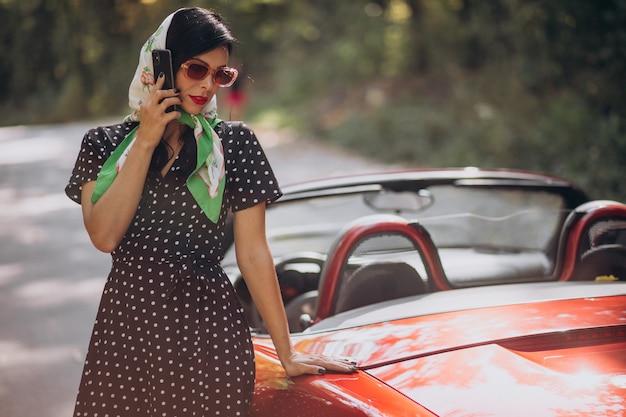 Linda mulher dirigindo um cabrio vermelho