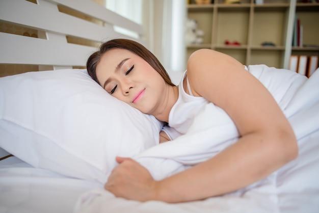 Linda mulher dorme no quarto, deitada na cama