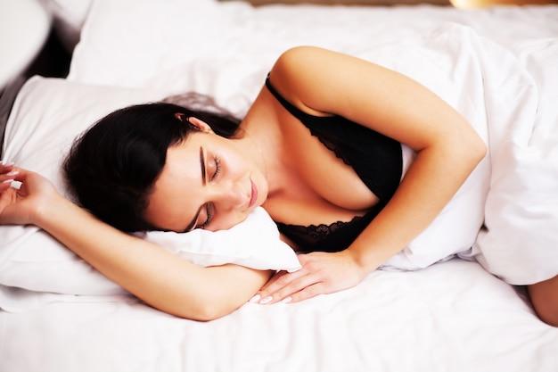 Linda mulher dormindo em casa no quarto brilhante