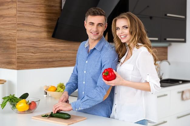 Linda mulher e o marido em pé cozinhando na cozinha de casa