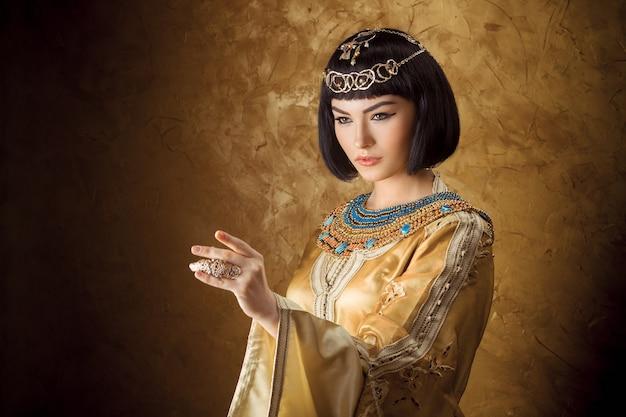 Linda mulher egípcia como cleópatra apontando o dedo para longe