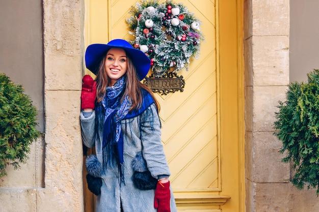 Linda mulher elegante com sorriso perfeito no chapéu azul e lenço andando na rua. mulher ficar perto da porta amarela com decorações de natal e inscrição de boas-vindas.