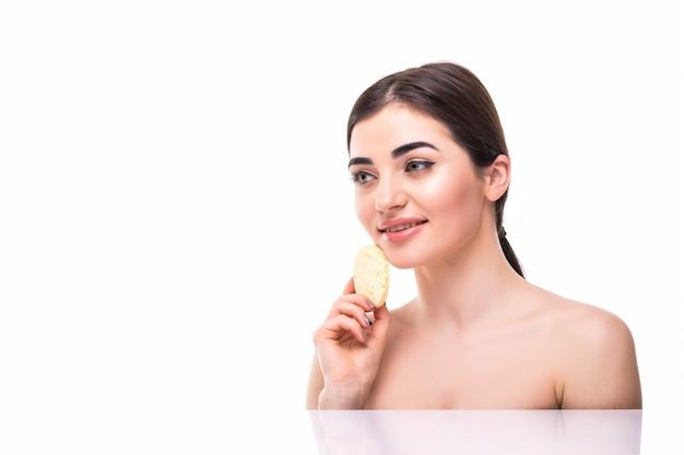 Linda mulher elegante com uma esponja nas mãos com os ombros nus cuidados com a pele isolado