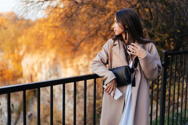 Linda mulher elegante em pé em um parque no outono