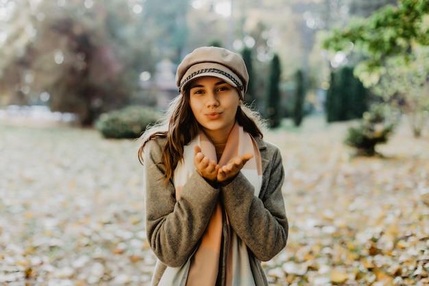 Linda mulher elegante em pé no parque no outono