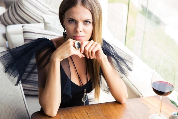 Linda mulher elegante sentada em um vestido de moda em restaurante