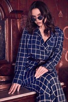 Linda mulher elegante, vestida com um terno xadrez azul no interior vermelho