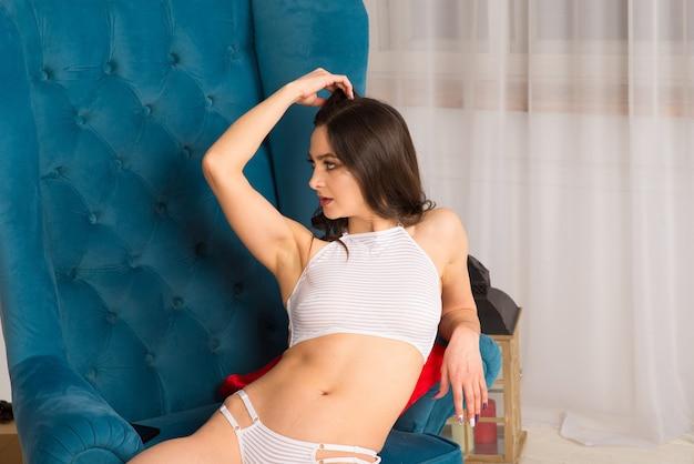 Linda mulher em lingerie perto do abeto de natal decorada