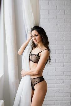Linda mulher em lingerie perto do abeto de natal em estúdio decorado