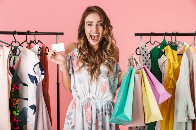 Linda mulher em pé perto do guarda-roupa, segurando sacolas de compras coloridas e cartão de crédito isolado em rosa