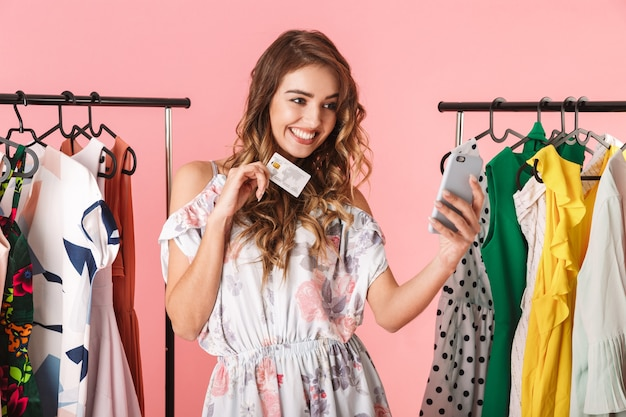 Linda mulher em pé perto do guarda-roupa, segurando um smartphone e um cartão de crédito isolado em rosa