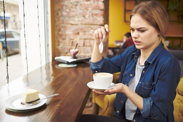 Linda mulher em um café, um copo de relaxamento de comunicação de bebida. foto de alta qualidade