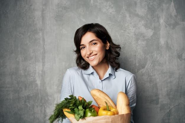 Linda mulher em um pacote de camisa azul com mantimentos na dieta alimentar de supermercado. foto de alta qualidade