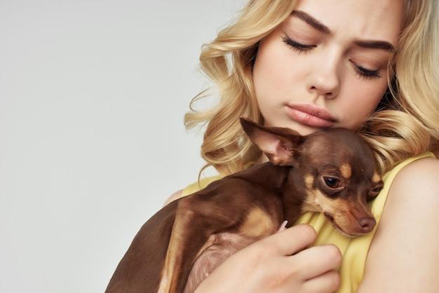 Linda mulher em um vestido amarelo divertido um cachorro pequeno vista recortada da moda. foto de alta qualidade
