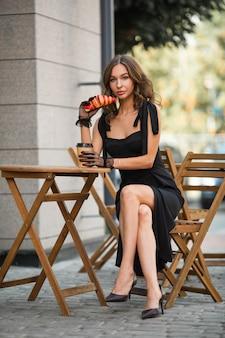 Linda mulher em um vestido com um croissant e café