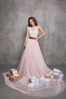 Linda mulher em um vestido longo rosa e com presentes