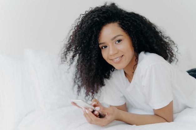 Linda mulher encaracolada com pele escura, sorriso terno no rosto, encontra-se na cama branca, veste camiseta, relaxa com tecnologias modernas