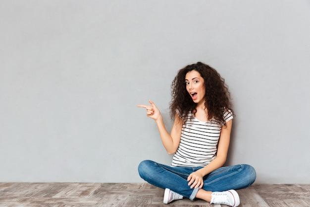 Linda mulher encaracolada em roupas casuais, sentado em posição de lótus no chão, apontando o dedo indicador de lado, enviando algo sobre o espaço da cópia de parede cinza