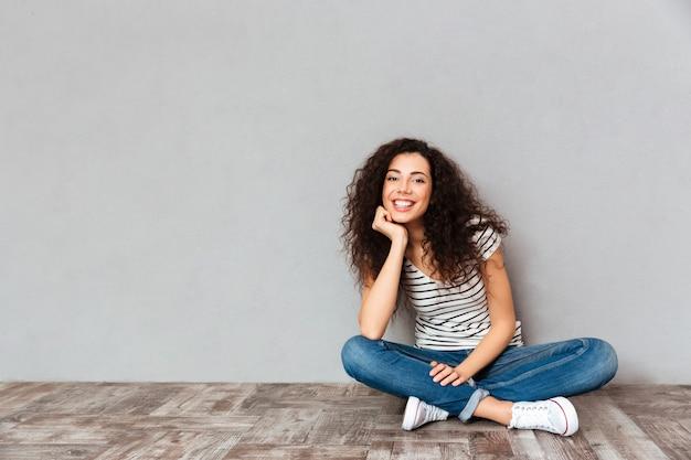 Linda mulher encaracolada em roupas casuais, sentado em posição de lótus no chão, sustentando a cabeça com a mão, sendo feliz e sincero sobre parede cinza