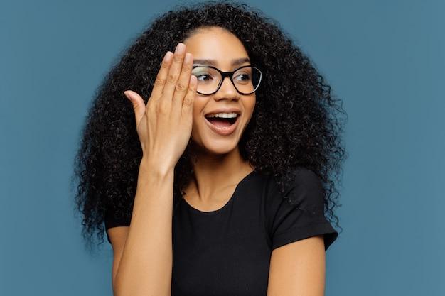 Linda mulher encaracolada olha de lado, toca o rosto, usa óculos transparentes, camiseta preta casual