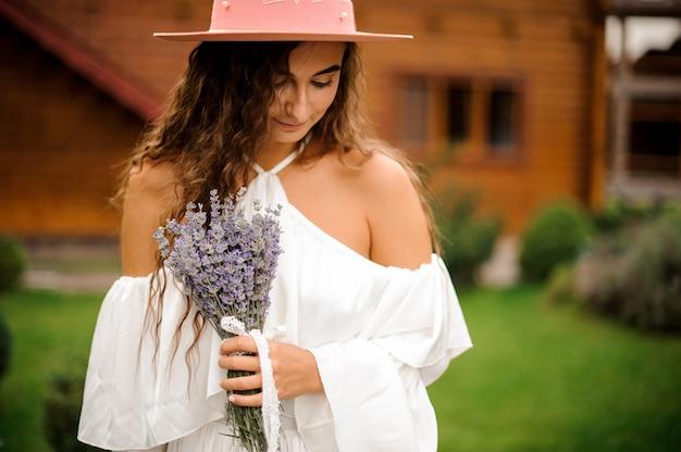 Linda mulher encaracolada, vestida com um vestido branco com buquê de lavanda