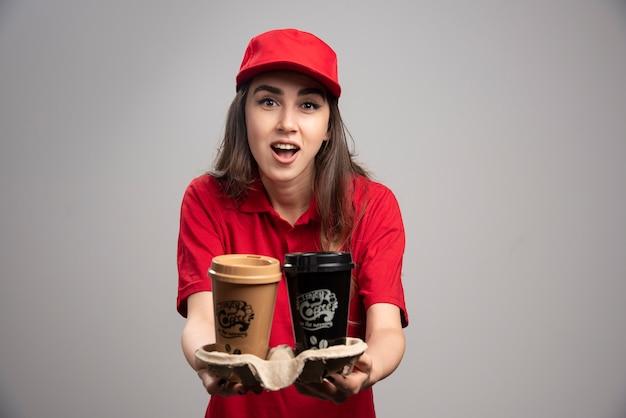 Linda mulher entregadora de uniforme vermelho, dando xícaras de café.