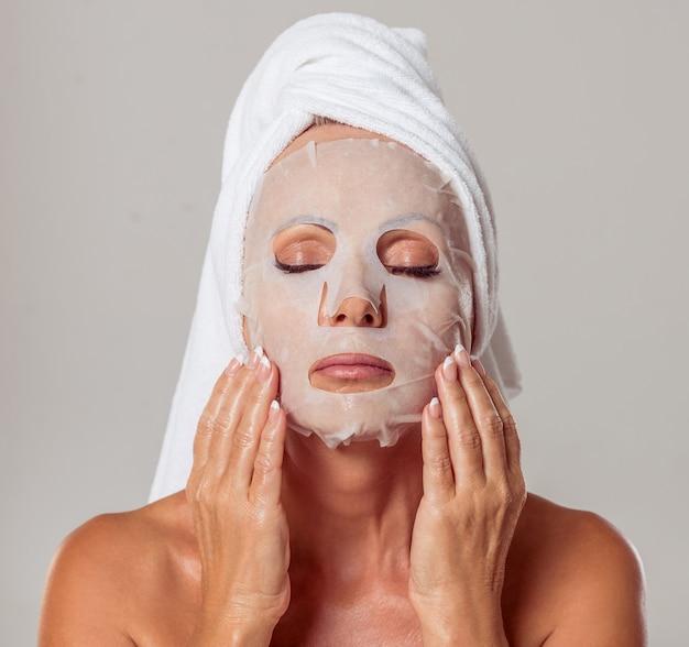 Linda mulher envelhecida média com uma toalha na cabeça dela.