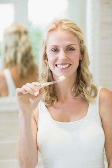 Linda mulher escovando os dentes no banheiro