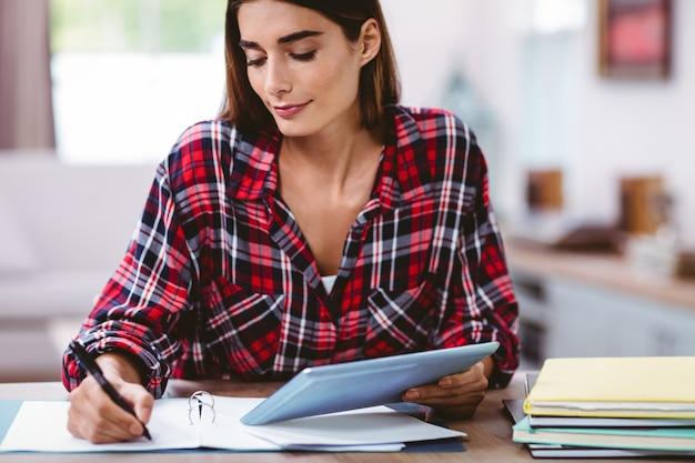 Linda mulher escrevendo no bloco de notas, mantendo o tablet digital