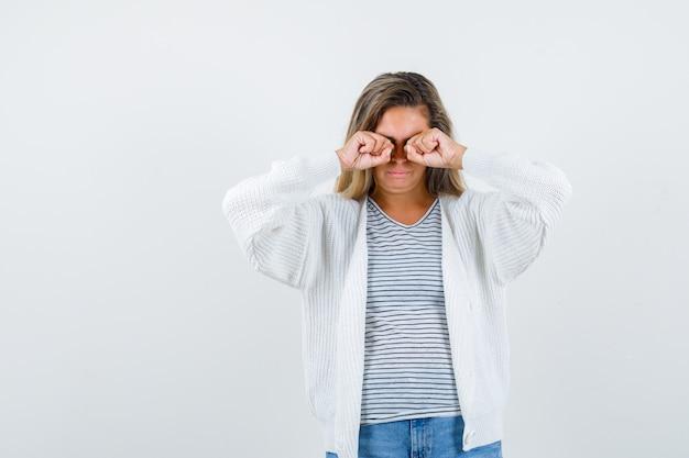 Linda mulher esfregando os olhos na jaqueta e parecendo triste, vista frontal.