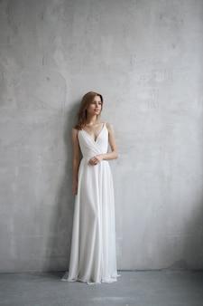 Linda mulher esguia em vestido de noiva branco