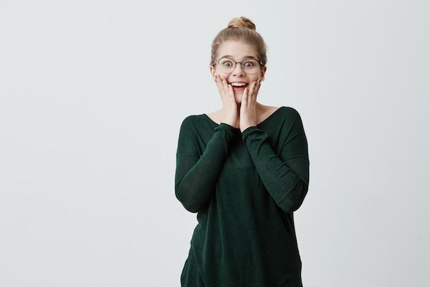 Linda mulher espantada com nó de cabelo loiro e óculos não consegue acreditar em seus olhos, feliz em receber presente inesperado do namorado, tem expressão feliz e surpresa. conceito de felicidade.