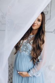 Linda mulher espera em poses de vestido azul em um estúdio