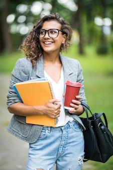 Linda mulher esperando amiga depois de ler literatura no campus da universidade