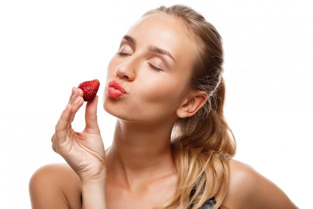 Linda mulher esportiva posando, comendo morango